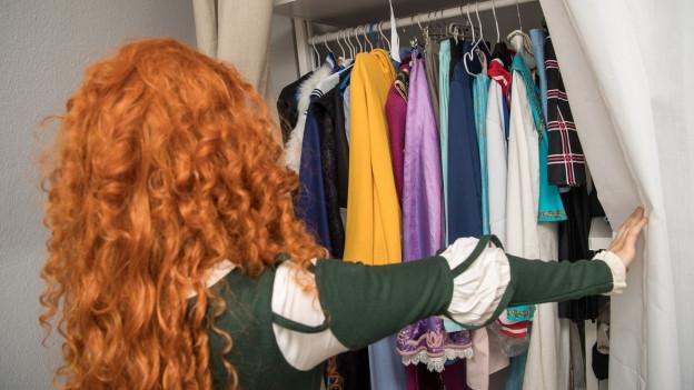 Frau blickt in Kleiderschrank voller Kleider