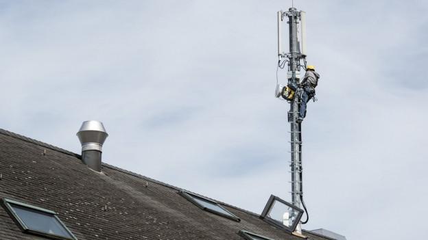 Ein Mann arbeitet an einer Mobilfunkantenne in Zürich.