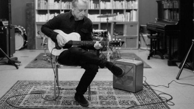 Hank Shizzoe mit Gitarre und Verstärker im Wohnzimmer