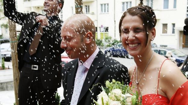 Ein Ehepaar wird mit Konfetti beworfen.