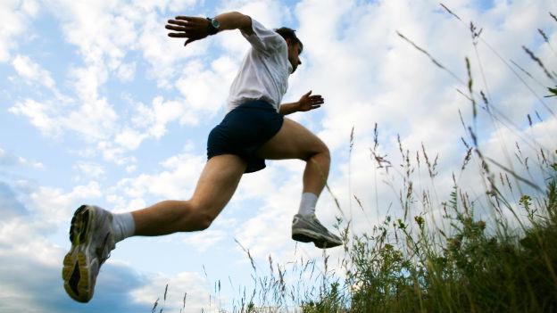 Mann rennt einen Berg hinauf.