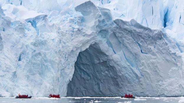 Ein riesiger Eisblock mit zwei kleinen Schlauchbooten im Vordergrund