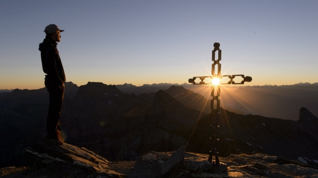 Auf einem Berggipfel blickt ein Mann in den Sonnenaufgang.