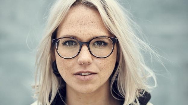 Portrait von Stefanie Heinzmann, mit Brille und Sommersprossen