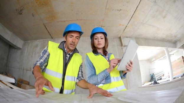 Mann und Frau mit Bauhelm vor Bauplänen.