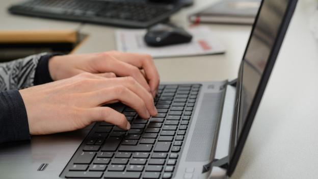 Weibliche Hände tippen auf einem Laptop