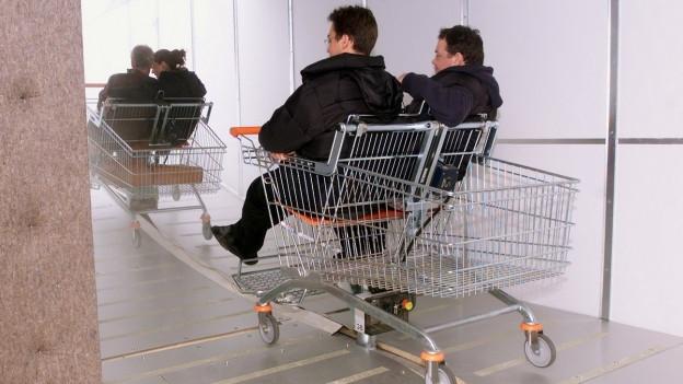 Ausstellungsbesucher werden in Einkaufswagen gefahren