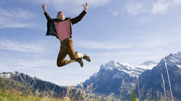 Mann springt vor Bergen in die Höhe.