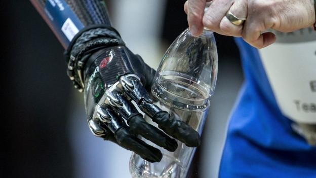 Eine Handprothese hält eine Wasserflasche