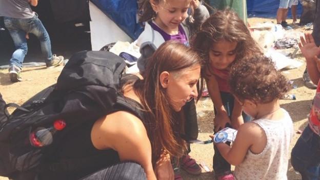 Eine Flüchtlingshelferin, umgeben von Kindern