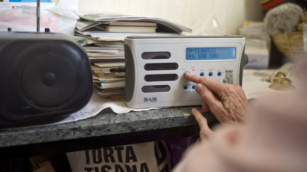 DAB+-Radio wird mit einer Hand eingestellt.
