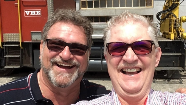 Zwei Männer vor einem Zug.