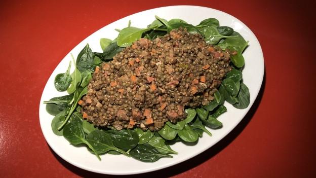 Linsensalat auf einem ovalen weissen Teller, mit Spinat garniert.