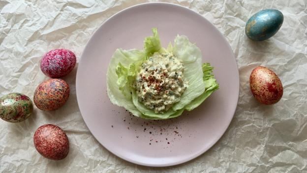 Eiersalat in einem Blattsalat serviert und bunt bemalte Ostereier.