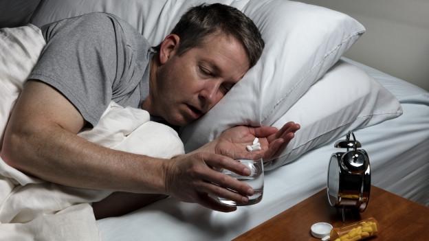 Mann im Bett, der eine Tablette nimmt