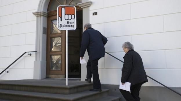 Zwei ältere Personen marschieren eine Treppe hoch in ein Abstimmungslokal. Vor der antiken Türe steht ein Schild, das eine Hand und die Aufschrift «heute Abstimmung» zeigt.