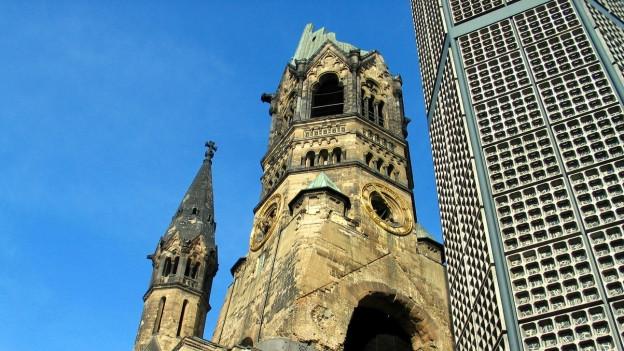 Die Berliner Gedächtniskirche mit zerbombtem Kirchturm, daneben der Neubau.