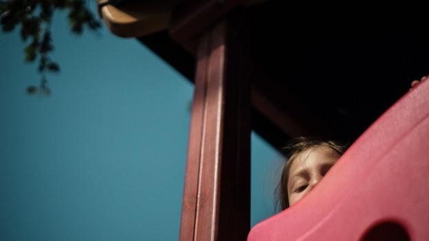 Kind guckt von Spielturm.