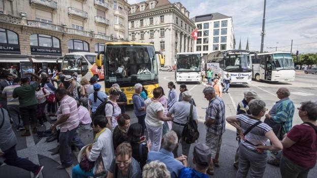 Viele Touristen warten in Luzern auf einen Bus.