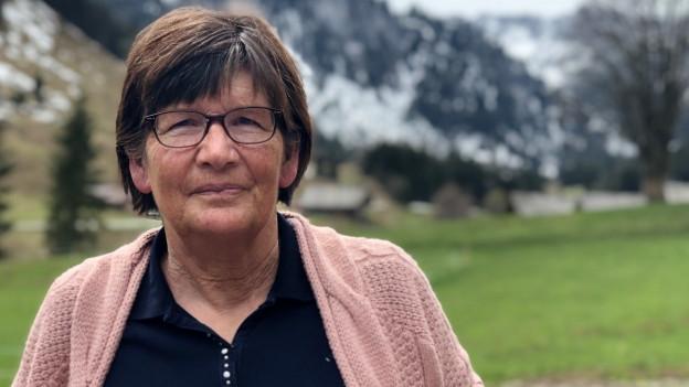 Erika Wiedmer-Mani vor ihrem Haus. Im Hintergrund sieht man die verschneiten Berge