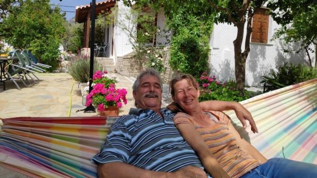 Eliane und Dimitri Apostolou sitzen in der Hängematte vor ihrem Haus.
