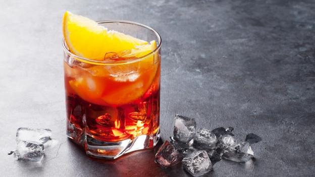 Ein Glas Negroni mit Orangenschnitz.