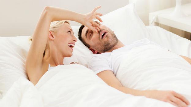 Frau hält Mann Nase zu im Bett.