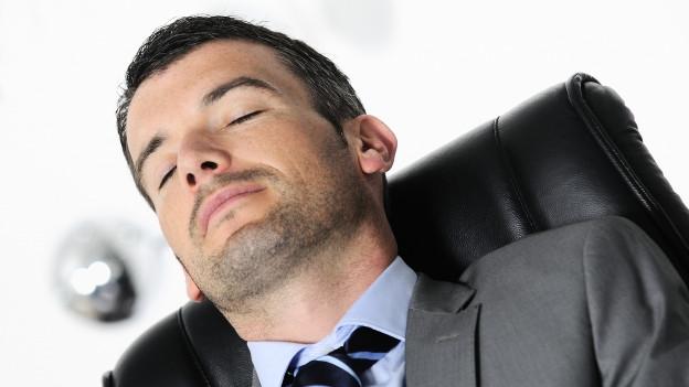 Mann mit Kravatte, der im Bürostuhl schläft