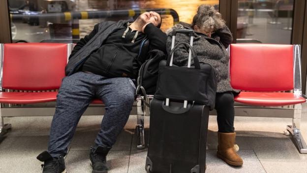 Zwei schlafende Menschen am Flughafen