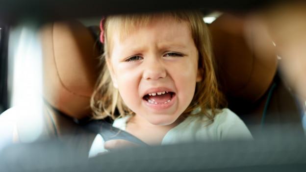 Blick durch den Rückspiegel auf ein kleines Mädchen im Kindersitz das weint