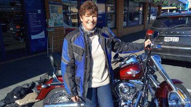 Renata Stent steht in Vollmontur vor ihrem Motorrad.