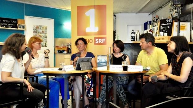Fünf Frauen und ein Mann sitzen um einen Tisch
