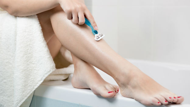 Frau rasiert sich die Beine.