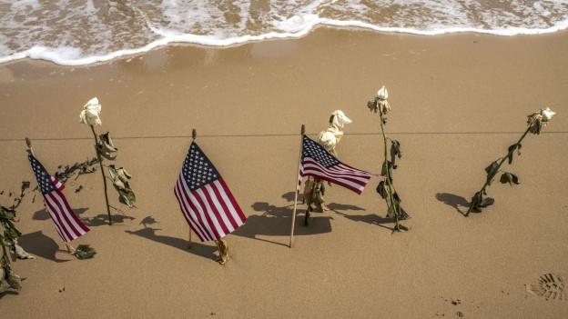 US-Flaggen und welke, weisse Rosen, stecken im Strand, dahinter Meer