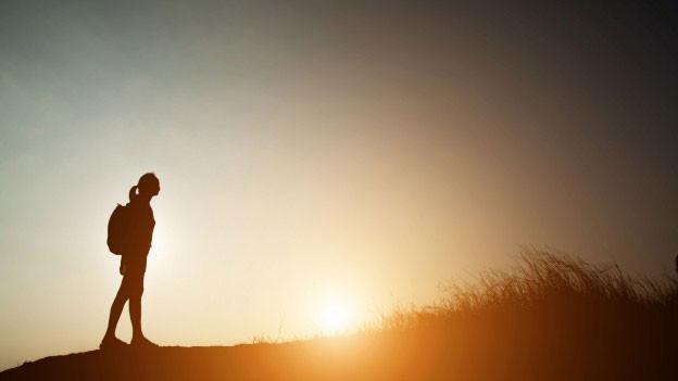 Eine Frau mit Rucksack wandert bei Sonnenuntergang.
