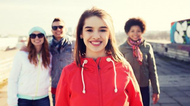Eine junge Frau. Im Hintergrund Familienmitglieder oder Freunde.