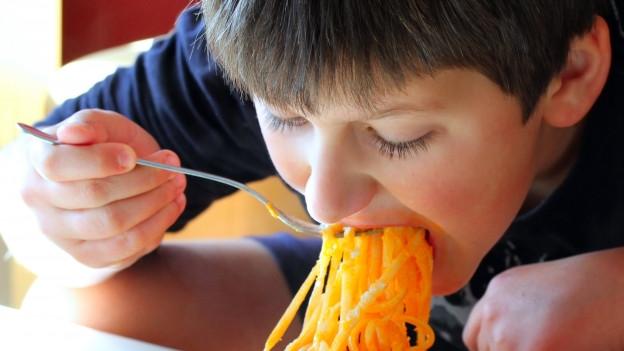 Ein junger Mann 'schlürft' Spaghetti in sich hinein