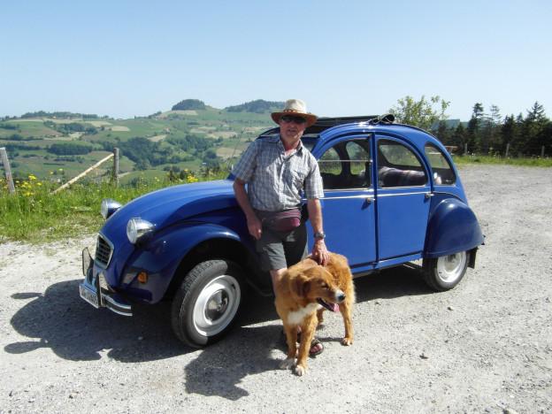 Ein Mann steht mit seinem Hund vor einem blauen 2CV6.