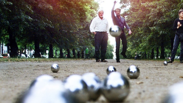 Nahaufnahme Pétanquekugeln im Vordergrund und Spieler im Hintergrund