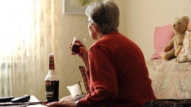 Eine Seniorin trinkt in ihrer Stube einen Cassis-Schnaps und schaut Richtung Fenster.
