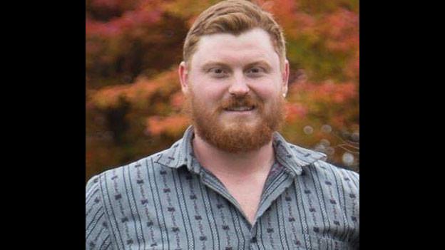 Portrait von Kyle Brönimann im karrierten Hemd.