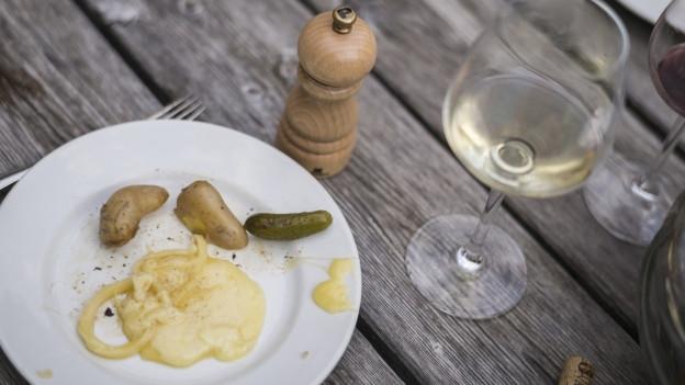 Ein Teller mit geschmolzenem Raclettekäse und Kartoffeln, daneben stehen ein Weinglas und eine Pfeffermühle.