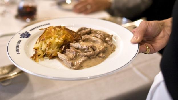 Eine Kellnerin hält einen Teller Zürcher Geschnetzeltes.