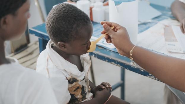 Einem kleinen Jungen wird eine Schluckmedizin verabreicht