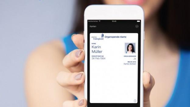 Frau hält Handy mit Organspendeausweis in die Kamera