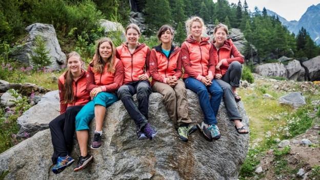 Sechs Frauen sitzen auf einem Findling.