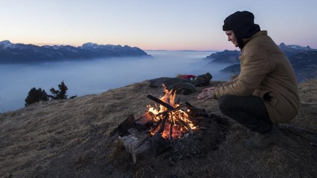 Ein Mann wärmt sich an einem Lagerfeuer auf einem Berg.