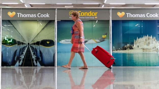 Eine Frau geht mit ihrem Koffer durch eine Flughafenhalle.