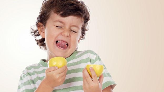 Junge beisst in Zitrone.