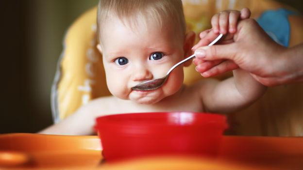 Kleinkind mit Löffel im Mund.